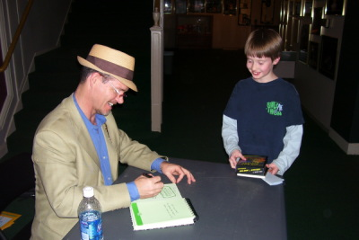 Bruce Hale signing a book for a young fan.
